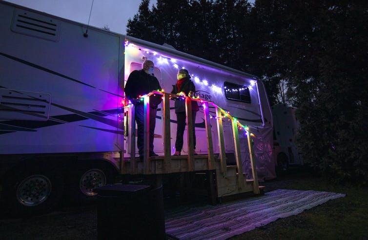 Un couple debout sur les marches de leur caravane au crépuscule, avec des lumières décoratives